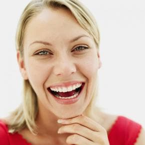 A woman in a red shirt with a BIG smile because she whitened her teeth safely at this Northern, VA dental clinic.