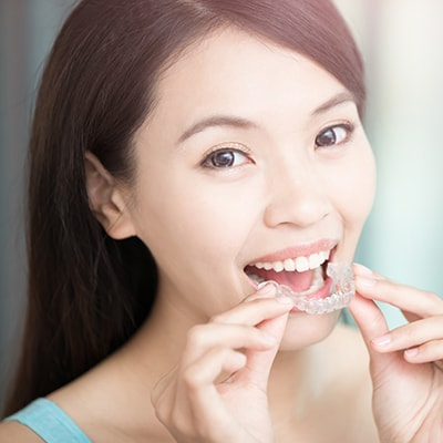 Woman putting on Invisalign aligners - part of our comprehensive dentistry in Northern, VA at Burke Centre Dental Arts