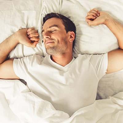 Mobile image of man sleeping peacefully while wearing a night guard