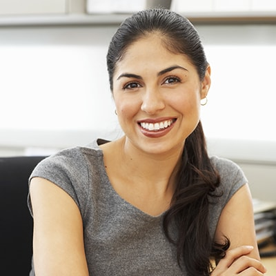 Mobile image of smiling woman after getting a scaling and root planing