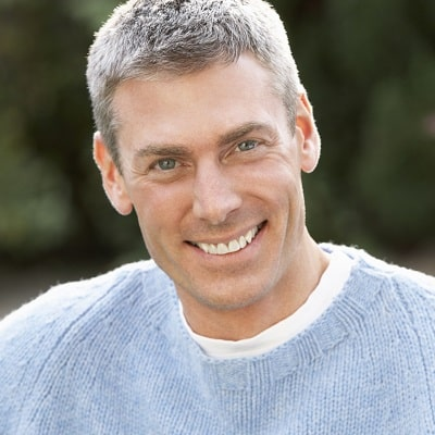 Mobile image of smiling man in blue sweater.