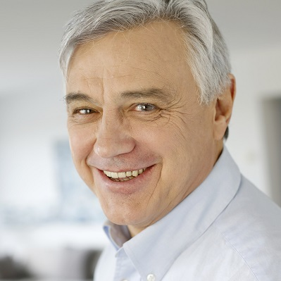 Mobile image of smiling, grey-haired man.