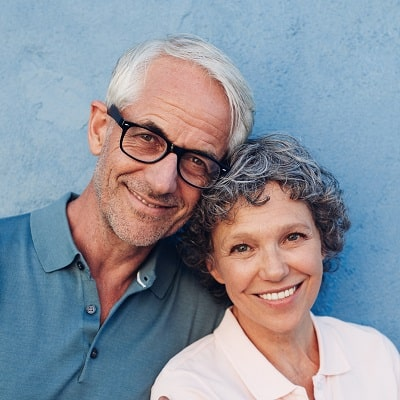 Older couple smiling with full smiles because of implant dentistry.