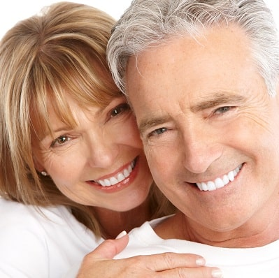 Mobile image of smiling man and woman in white shirts.