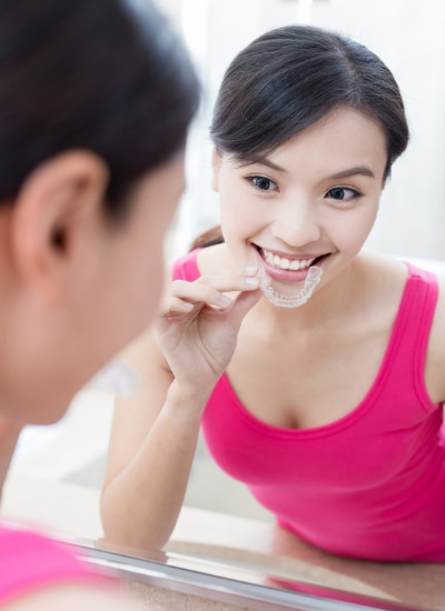 Young Asian girl in a pink tank top putting Invisalign clear aligners in to straighten her teeth