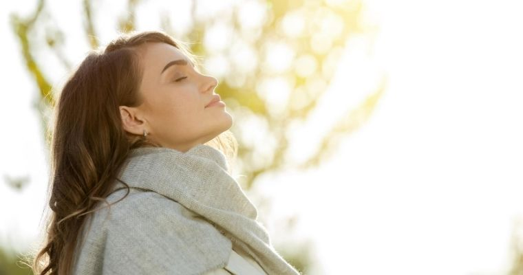 A woman standing outside breathing in air, relaxing about getting dental care with SleepGuardian anesthesia