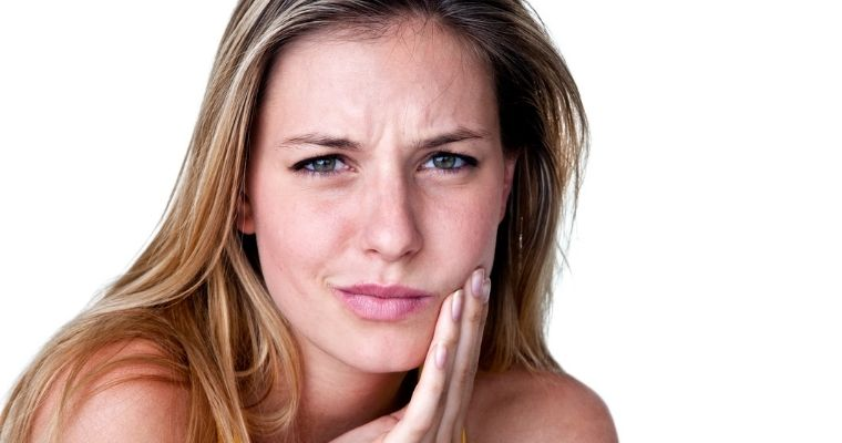 Woman touching jaw area in pain